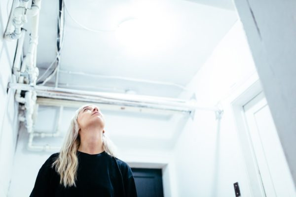 woman staring at pipes on ceiling - premier heating and cooling